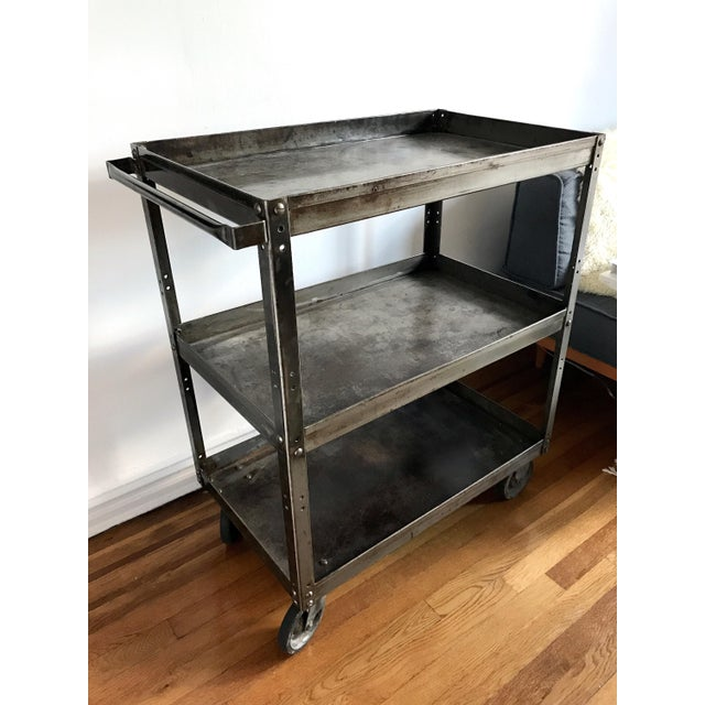 An antique metal bar cart with rolling wheels and handle could be used for barware or as additional shelving. Adds a great...