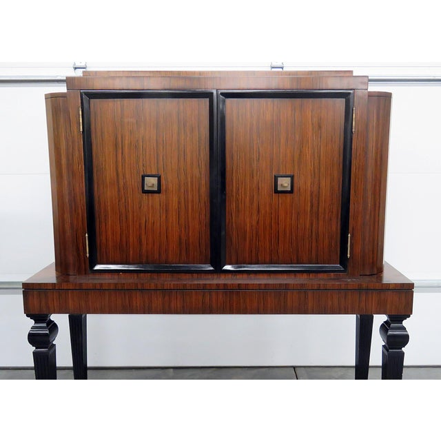Art deco style rosewood bar with ebonized legs and accents. Each side door holds 1 glass shelf. The center doors contain 2...