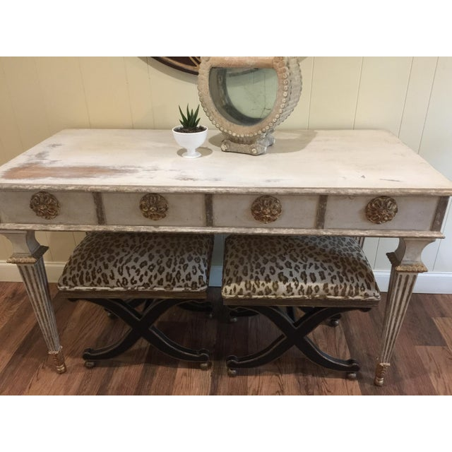 This item is an Amy Howard large console table with medallions across the apron and tulip legs. The finish is a soft off...
