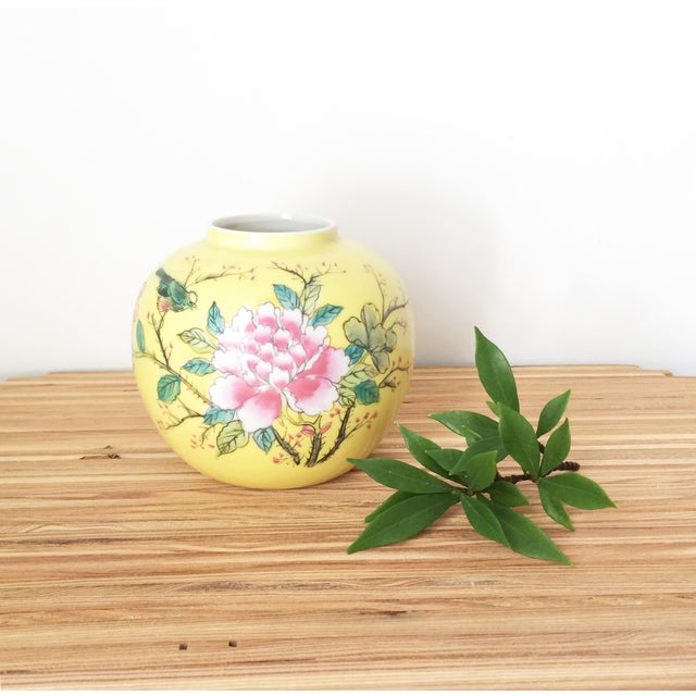 A lovely small vibrant yellow Japanese porcelain ware vase with a flowering pink tree branch and bird hand painted on the...