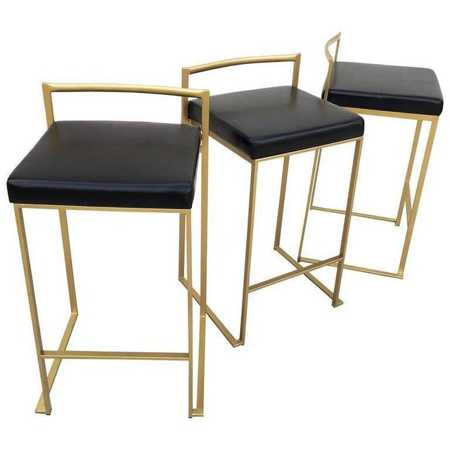 Minimalist bar stools in gold painted frame with black leather seats designed by Enzo Berti and produced by LaPalma,...