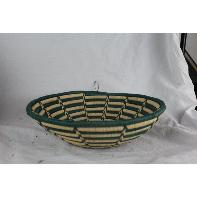 Handwoven rattan swirled tribal basket with starburst design in green and tan. The piece is from the mid 20th century.