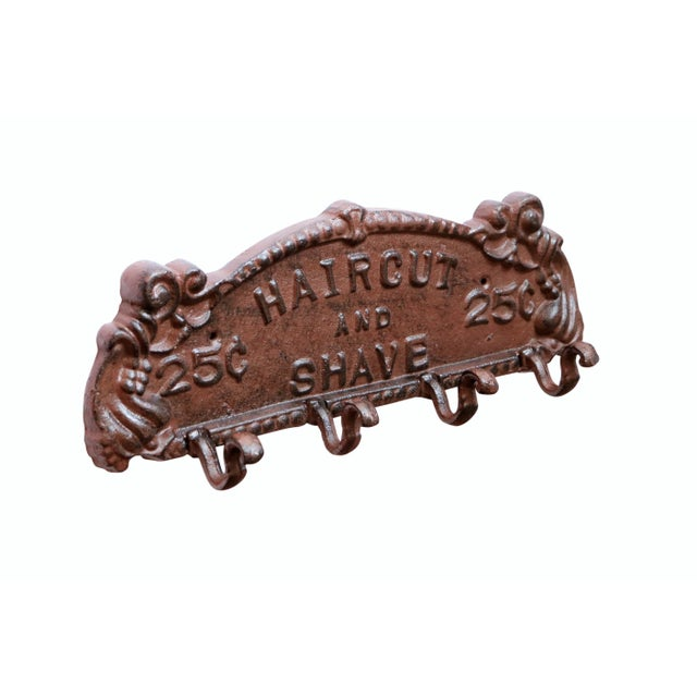 """A cast iron wall plaque with four hooks. The plaque is demilune shaped with a pie crust edge and reads """"Haircut and Shave""""..."""