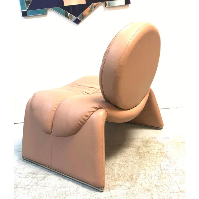 A pink leather postmodern lounge chair. Round back on a simple waterfall seat with chrome feet. Very plush.