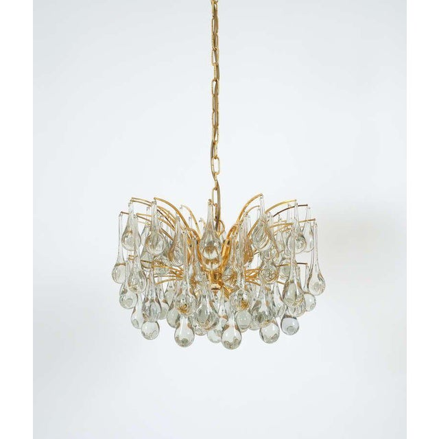 Beautiful multi-tiered tear drop chandelier composed of a multitude of handblown smooth Murano glass drops hanging from a...