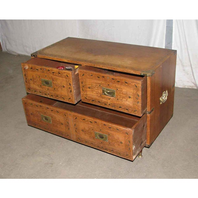 Solid wood chest of drawers with intricate inlaid brass details.