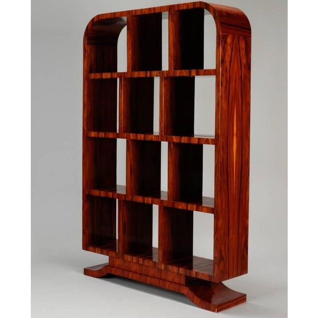 This is an Art Deco arched top burl wood polished étagère. The piece features a footed pedestal base and four shelves with...