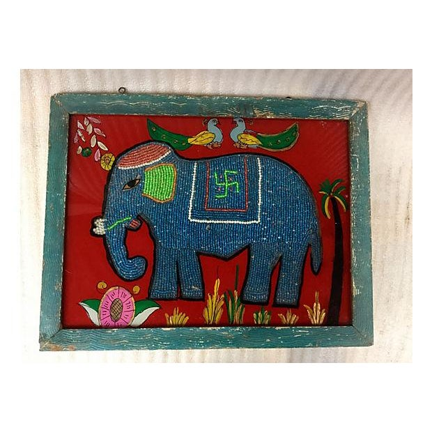 An Indian églomisé (reverse painting) of a elephant with beading. Displayed in a worn wood frame.