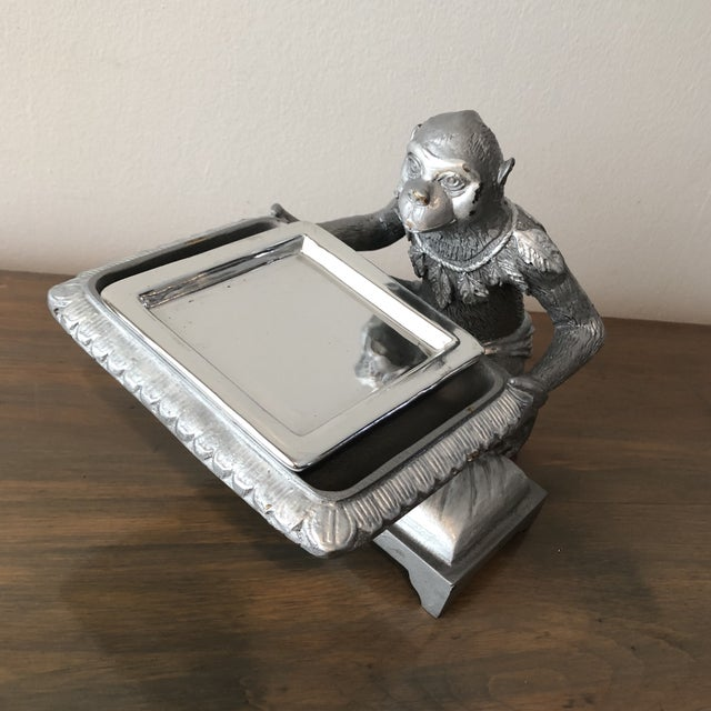 Fantastic silver colored vintage monkey sculpture holding a tray. Resting his knee on a pillow he is holding a silver tray...