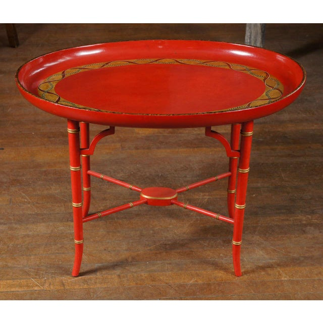 English scarlet and gilt decorated tray on later faux bamboo base. Coffee table.