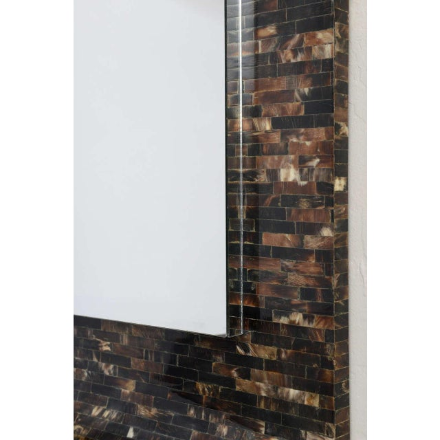 Self-framing horn tile mirror gently curves into a a shelf at the bottom to create a minimalist wall-mounted console....