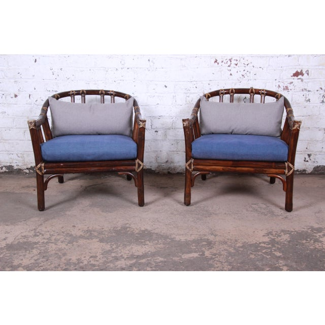 A gorgeous pair of mid-century Hollywood Regency club chairs by McGuire of San Francisco, circa 1978. The chairs are...