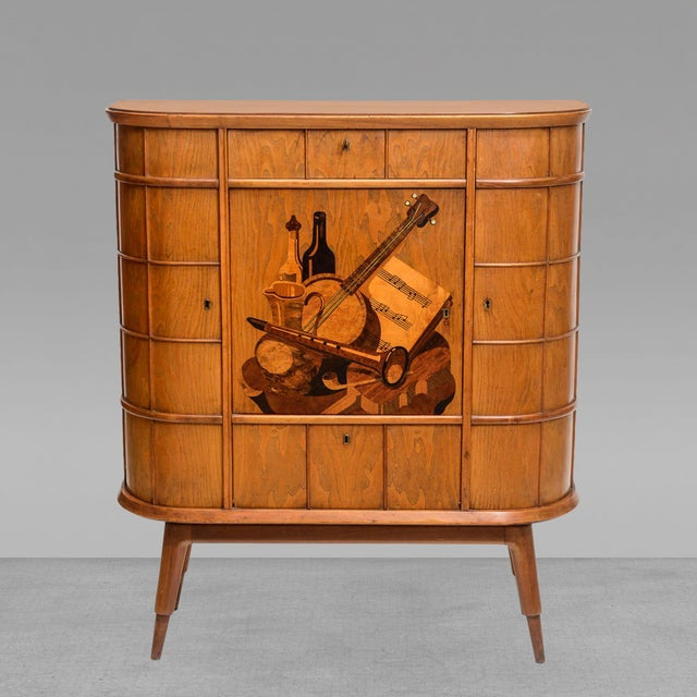 The demilune form with cross hatched raised panels of doors and drawers flanking a central revolving bar cabinet, inlaid...