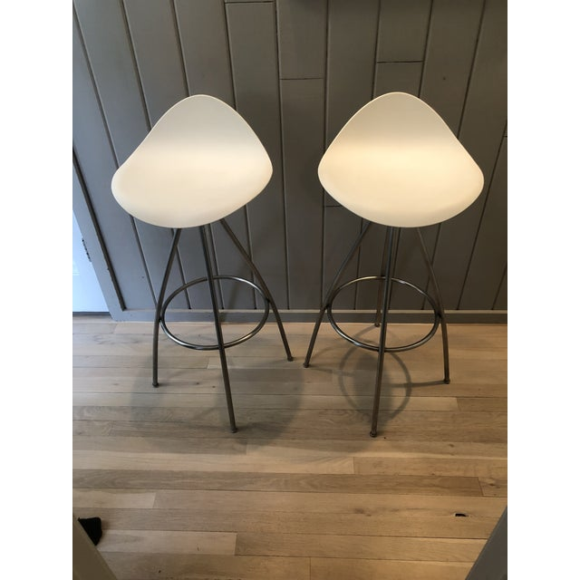 Jesús Gasca designed bar stools with matte stainless steel frame; molded plastic seat shell with white polypropylene...