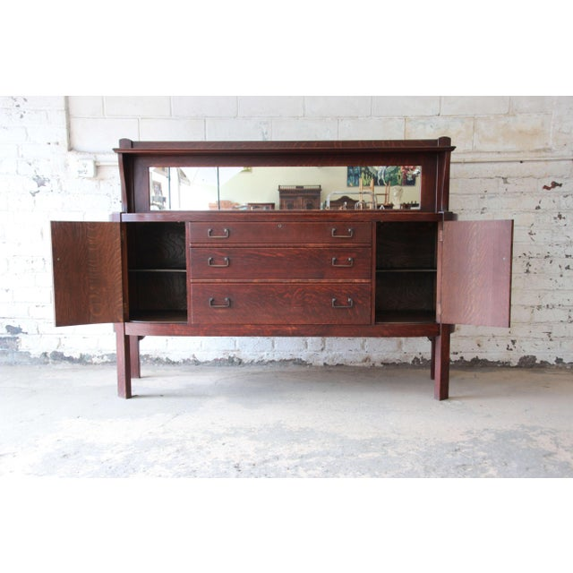 Offering a rare and stunning Mission quarter sawn oak sideboard credenza by Grand Rapids Chair Co. The sideboard feature...