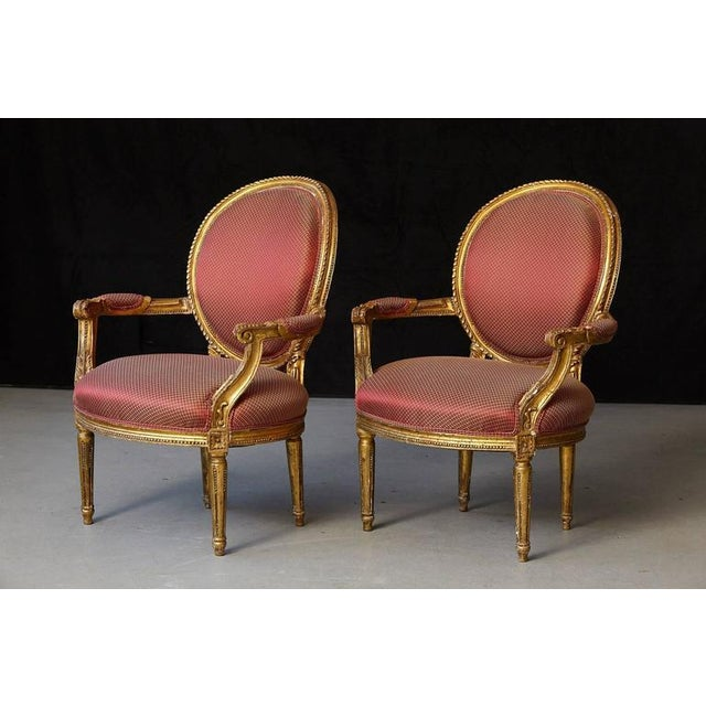 Beautiful looking pair of French Louis XVI style gilded fauteuils with carved relief ornaments. Some loss to the gild,...