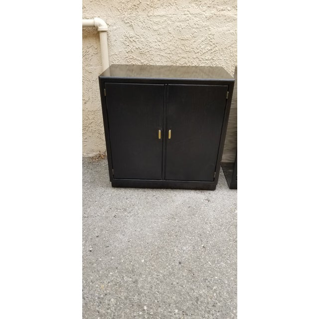 Vintage mid century cabinets with original brass hardware have been refinished with black stain for a sleek lacquer...