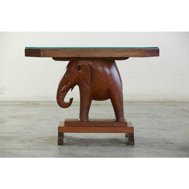 This rare octagonal wooden table with a base consisting of a carved figure of an elephant (with eyes made of bone, one is...