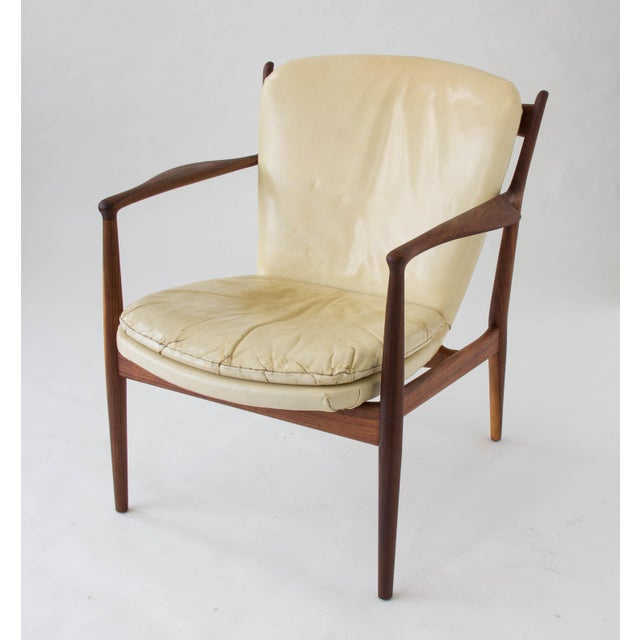 """Designed in 1951, this model FJ51 or """"Delegate Chair"""" by Finn Juhl and manufactured by Baker Furniture has a delicate teak..."""