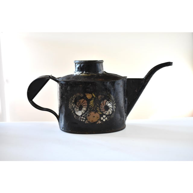 A rare, c. 1830s early Americana black toleware or tole metal watering pot, with a stenciled design of flowers in gold and...