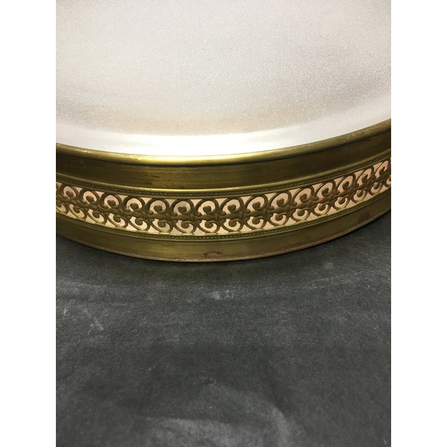This lovely flush mount ceiling light has beautiful brass fretwork on the band and plain frosted glass . The patina has...