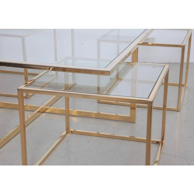 Beautiful coffee table with four nesting tables in brass by Maison Charles. The glass plates are loosely inserted to...