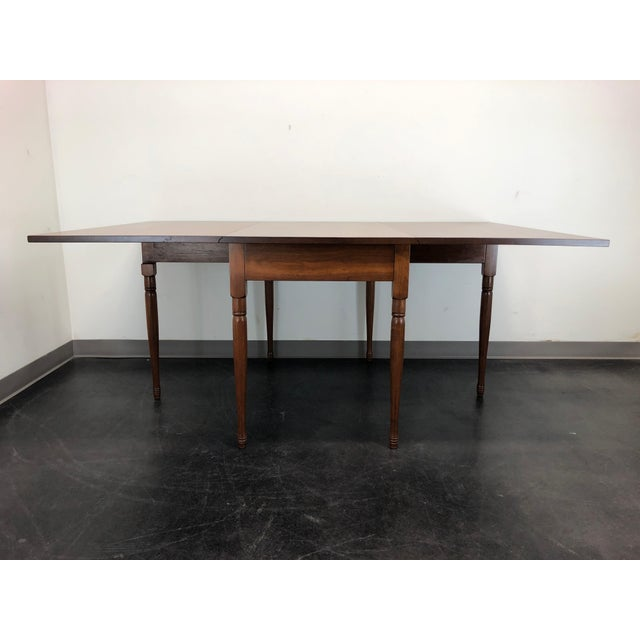A gateleg drop leaf dining table in solid Walnut by EA Clore Sons of Madison, Virginia. Made in the USA in the late 20th...