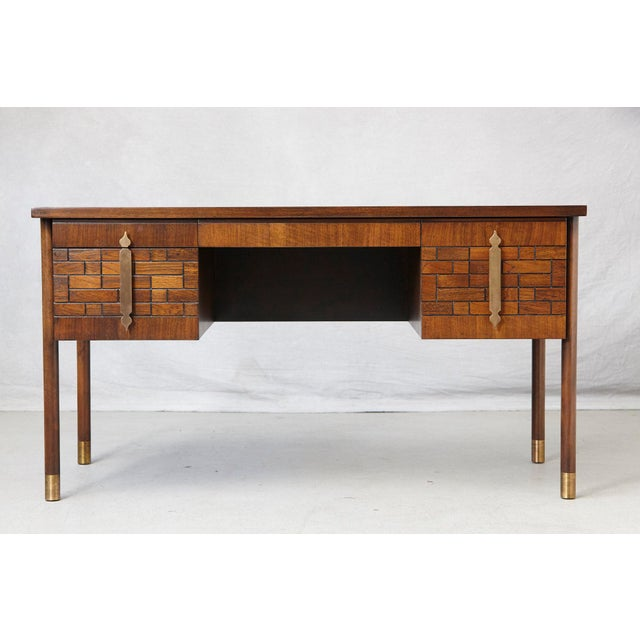 Impressive walnut desk with four drawers, graphic wood work on the drawers, wood inlays on the top and brass hardware,...