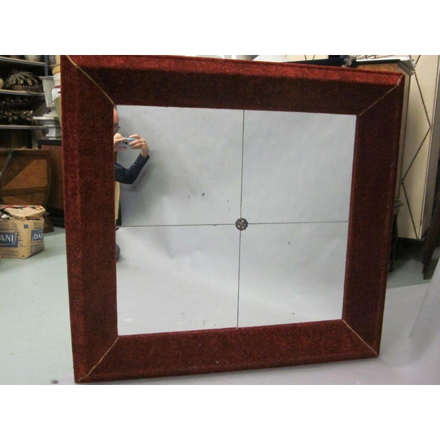 A stunning Venetian wall mirror with an angular frame upholstered in antique velvet and composed of four naturally...