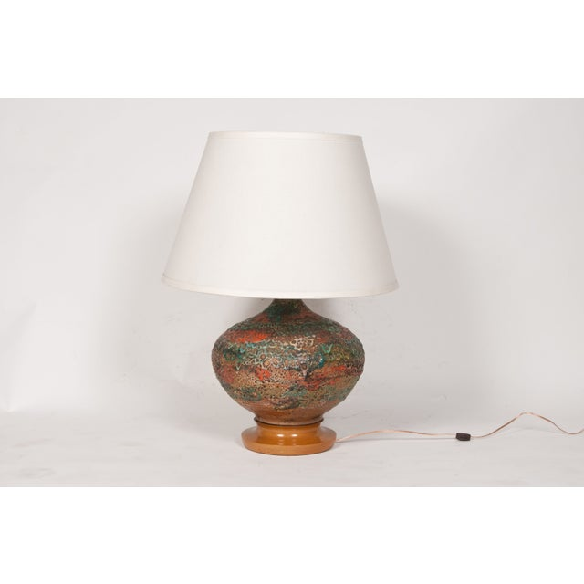 Interesting table lamp with a 1950s volcanic glaze technique. Custom shade included. Wired and in working condition. Base,...