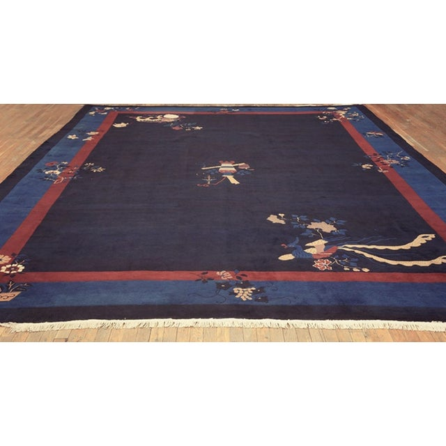 Antique Chinese - Peking Rug with a navy background and blue border.