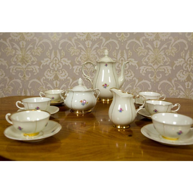 Smooth porcelain in a shade of ecru with gildings, ornamented with a subtle floral motif. The service includes: 6 cups,...
