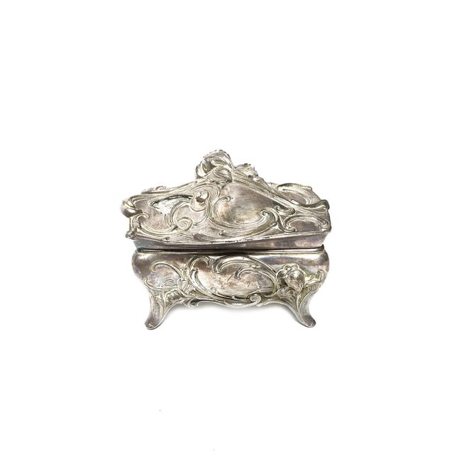 Art nouveau cast metal footed jewelry casket box elegant floral motifs and original cream fabric lining. This heavy ornate...