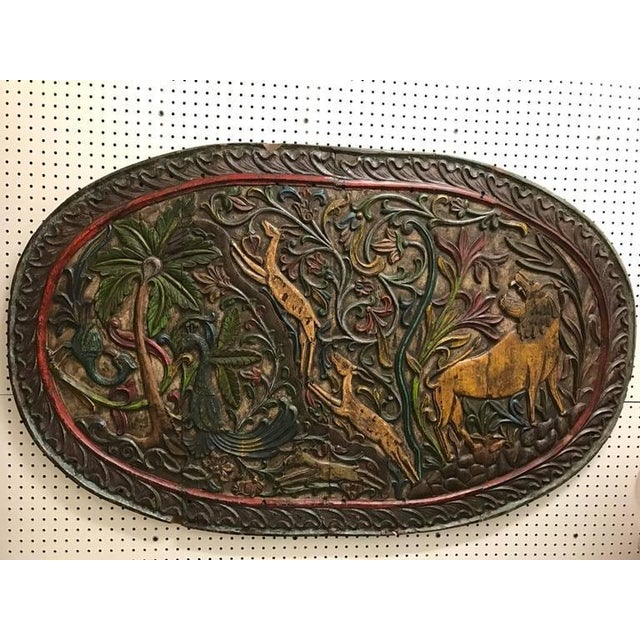 Carved wood plaque depicting animals. Having exotic animals including birds, lions and gazelles.