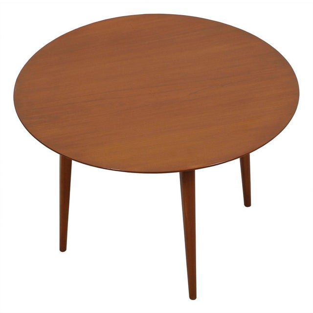 This simple yet beautiful round coffee table is in the style of Danish designer Hans Wegner. The round top has a thin edge...