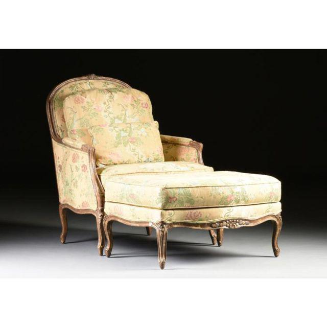 This Louis XV-style bergere has carved rails and floral carved knees ending on short cabriole legs, with a matching shaped...