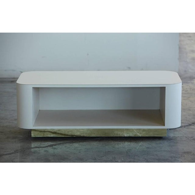 Custom-made media center on casters in white laminate with rounded corners and decorative brass board.