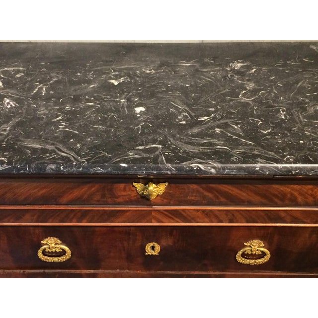 This regal chest of drawers has flame mahogany wood, bright gold hardware and dark gray marble top. In excellent...