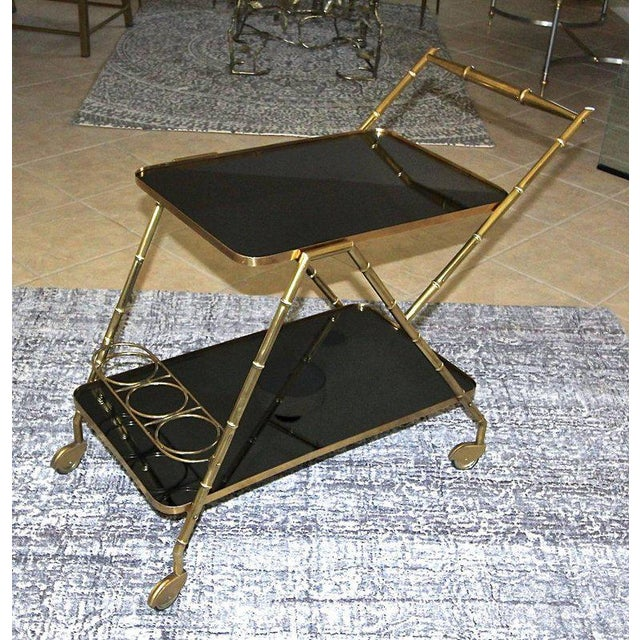 1950s Italian brass faux bamboo two-tier bar or serving cart with newer dark charcoal mirrored inserts. Good condition...
