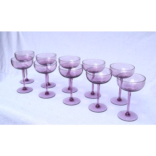 A set of ten elegant crystal champagne coupes with lithe faceted stems. Unusual amethyst color.