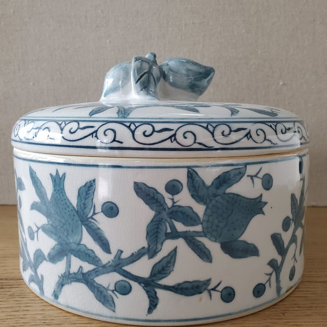 A lidded Chinoiserie vessel crafted of ceramic pottery. The pattern is hand painted branches bearing fruit with a fruit...