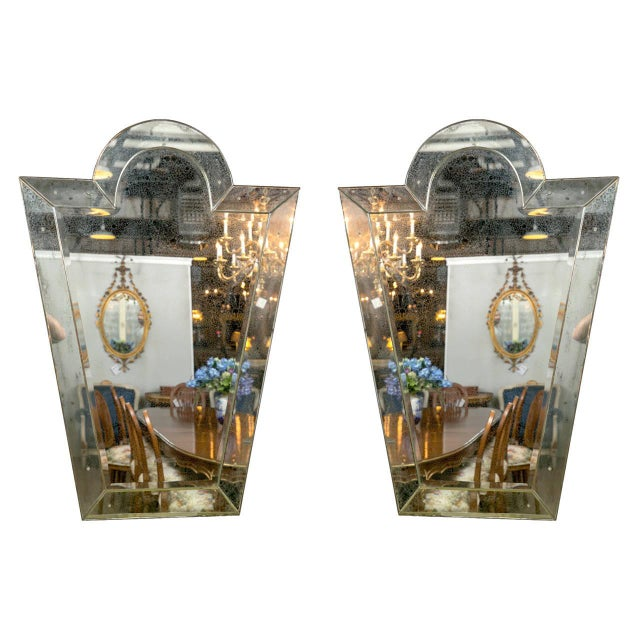 A pair of Venetian key hole shaped mirrors. The center beveled panel mirror flanked by six beveled sided mirrored panels....