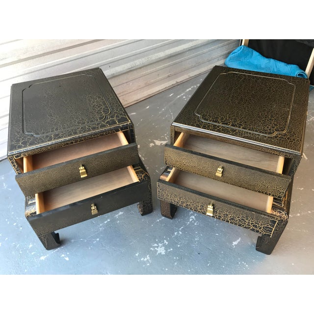 Handsome Asian inspired end tables by Lane furniture. Both tables resemble a chest on stand. Tables feature a gold crackle...