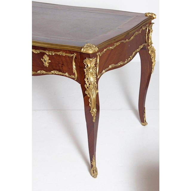 A elegant French Late 19th century Louis XV style rosewood and ormolu bureau plat. The top is a gilt tooled shaped leather...