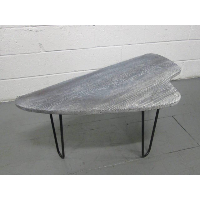French, cerused coffee table. Has an organic form with wrought iron hairpin style legs.