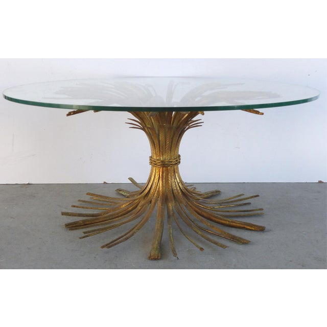 Offered is a Mid-Century Modern gilt iron coffee table in the form of a sheaf of wheat with a round glass top. Made in...