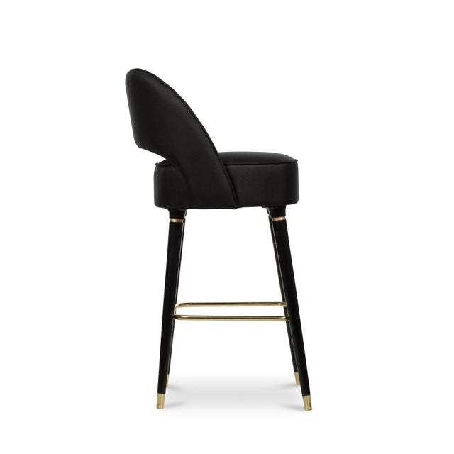 Collins is a crescent open back bar chair designed with sleek mid-century modern lines. It has glamorous glossy black...