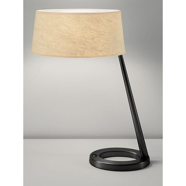 Modern style lamp in black bronze. Oval hollow bases and tapered columns. Desk lamp has colour co-ordinated push switch in...