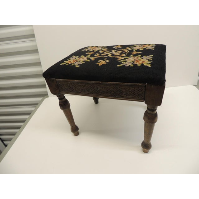 Footstool with Louis XVI style fluted legs and reupholstered with a floral black antique tapestry with flowers; carvings...