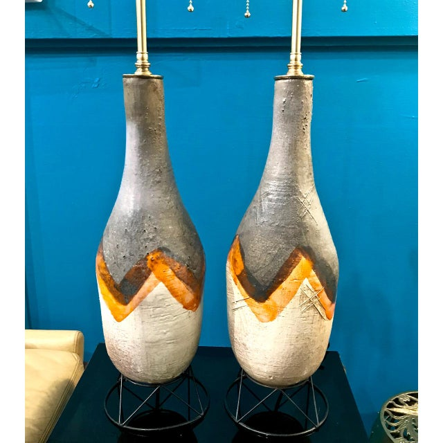 Great pair of midcentury Italian or American glazed terra cotta lamps. The pottery bases have been raised on crafted wire...